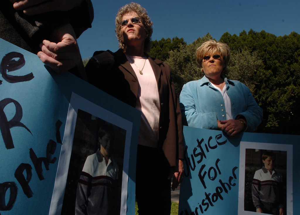 . Mary Ann Hughes, left, and her sister Jane Carlone, right, stand outside the Bronco Student Center to support the death penalty at Cal Poly in Pomona February 9, 2005. Kevin Cooper alleged murdered the son of Mary Ann Hughes in Chino Hills.  (Staff photo/Inland Valley Daily Bulletin)