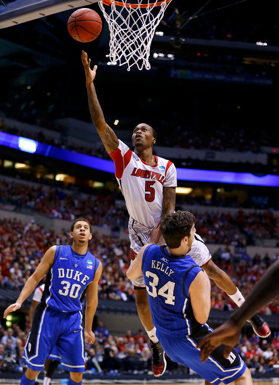 . Louisville Cardinals guard Kevin Ware (5) goes to the basket over Duke Blue Devils forward Ryan Kelly (34) in the first half during their Midwest Regional NCAA men\'s basketball game in Indianapolis, Indiana, March 31, 2013. REUTERS/Jeff Haynes