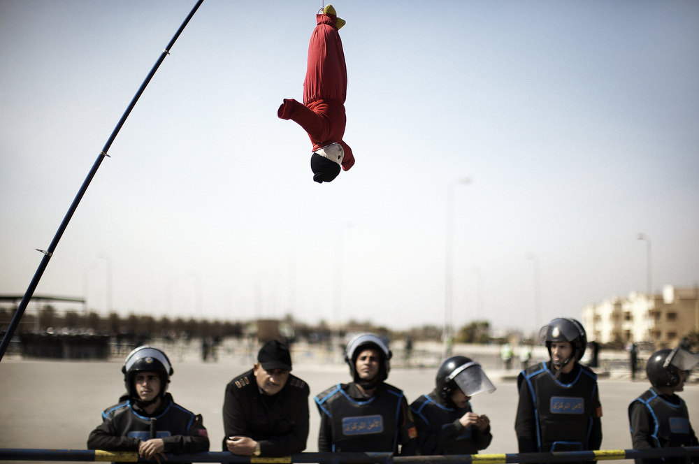 Description of . Egyptian riot policemen look at a hanged puppet, held up with a fishing rod by an anti-Hosni Mubarak demonstrator, outside the court in Cairo on February 22, 2012, as the landmark murder and corruption trial of the former president entered its final day of hearings, with the judge expected to announce the date of the verdict. Cameras are not allowed inside the courtroom and state television did not show Mubarak or the defendants arriving in court. MARCO LONGARI/AFP/Getty Images