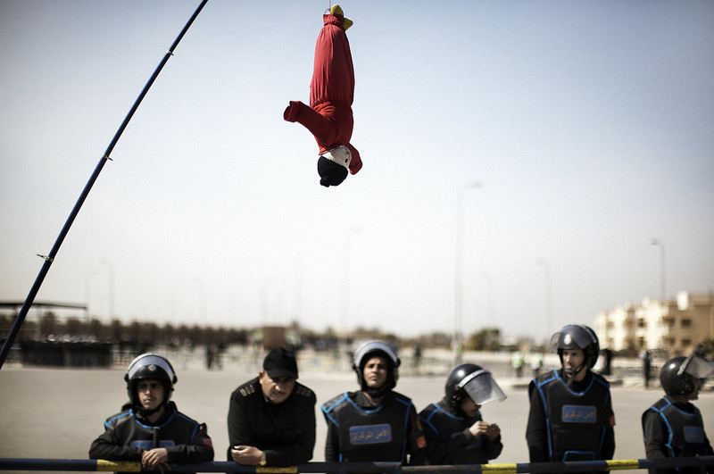 . Egyptian riot policemen look at a hanged puppet, held up with a fishing rod by an anti-Hosni Mubarak demonstrator, outside the court in Cairo on February 22, 2012, as the landmark murder and corruption trial of the former president entered its final day of hearings, with the judge expected to announce the date of the verdict. Cameras are not allowed inside the courtroom and state television did not show Mubarak or the defendants arriving in court. MARCO LONGARI/AFP/Getty Images