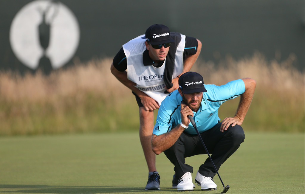 . Dustin Johnson of the US and his caddie Austin Johnson line up a putt on the 18th green during the second day of the British Open Golf championship at the Royal Liverpool golf club, Hoylake, England, Friday July 18, 2014. (AP Photo/Peter Morrison)