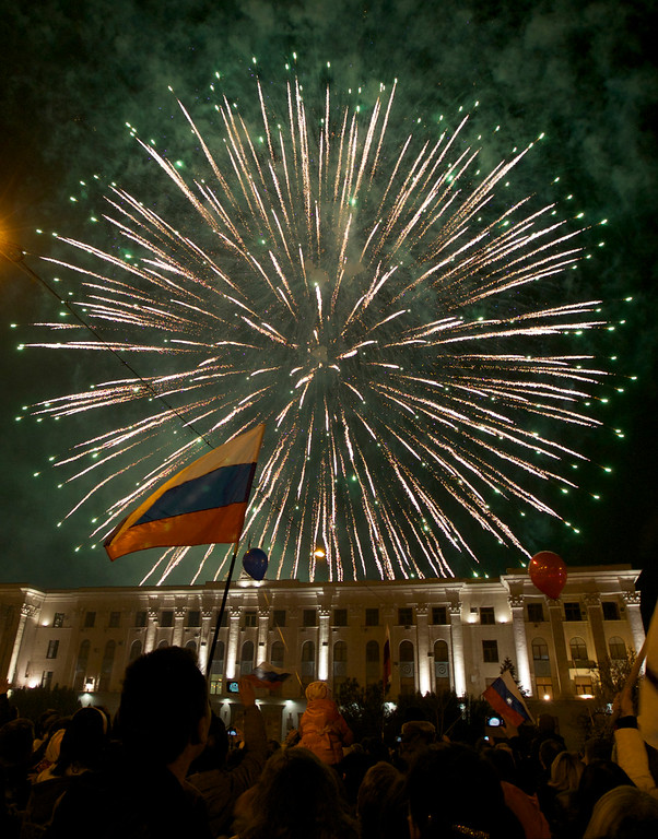 . People watch fireworks at the central Lenin square in Simferopol, Crimea, on Friday, March 21, 2014.  Russian President Vladimir Putin completed the annexation of Crimea on Friday, signing a law making the Black Sea peninsula part of Russia.(AP Photo/Ivan Sekretarev)