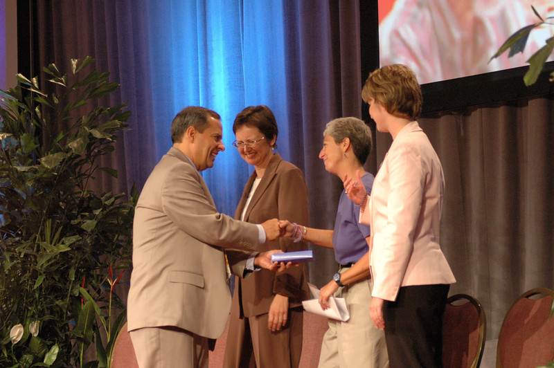 Carlos Peña (Vice President, ELCA) presents Kathryn Wolford (President, Lutheran World Relief) with a gift.