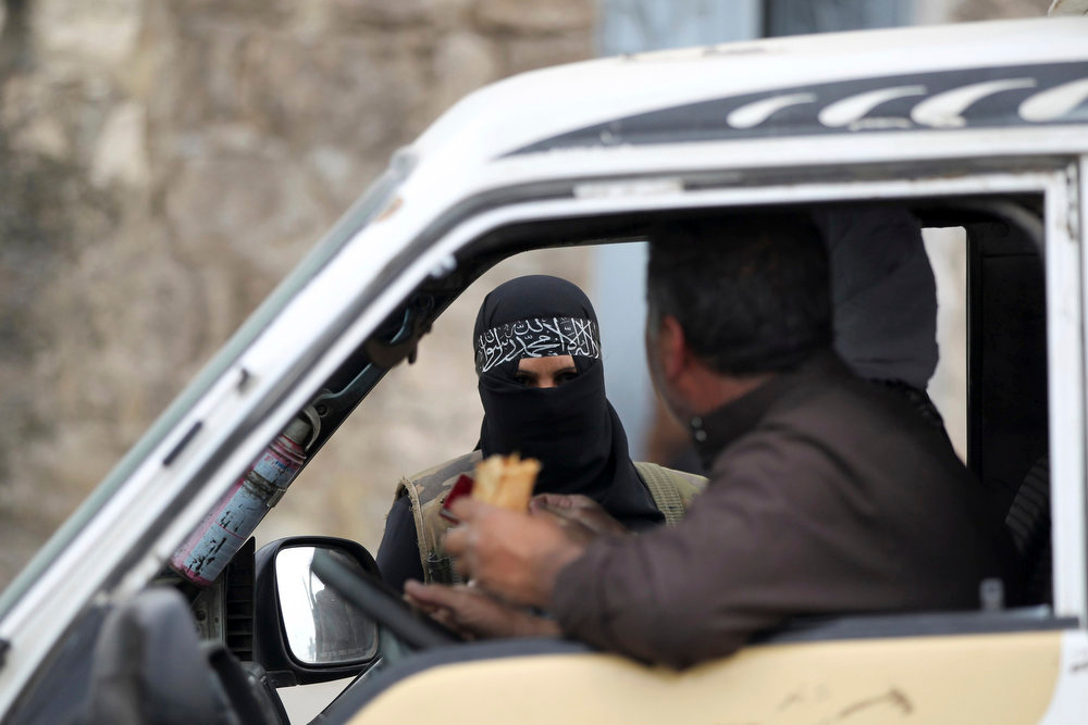. A woman member of the Al-Ikhlas (Loyalty) Battalion, stops a van at a checkpoint in Aleppo March 31, 2013. The Al-Ikhlas (Loyalty) Battalion is a security battalion that involves women that are in charge of erecting sudden checkpoints and raiding houses that contain women in Aleppo. The battalion is under the Ghorabaa (Strangers) Al-Sham Front, controlled by the Free Syrian Army.   REUTERS/Giath Taha