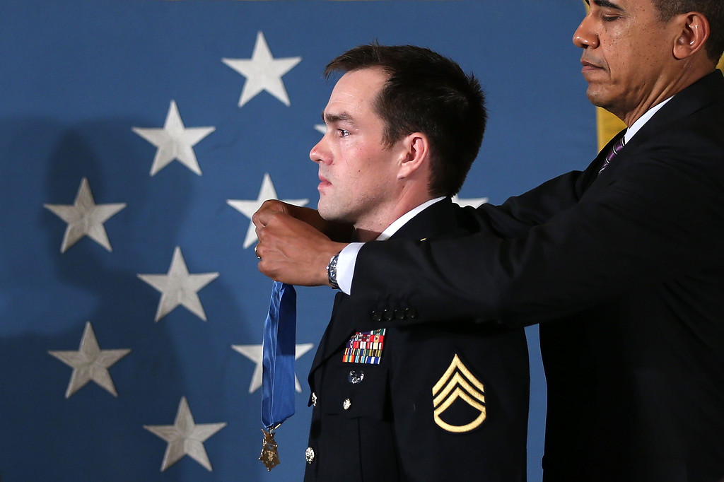 . U.S. President Barack Obama (R) presents the Medal of Honor for conspicuous gallantry to Clinton Romesha, a former active duty Army Staff Sergeant, at the White House February 11, 2013 in Washington, DC.  (Photo by Alex Wong/Getty Images)