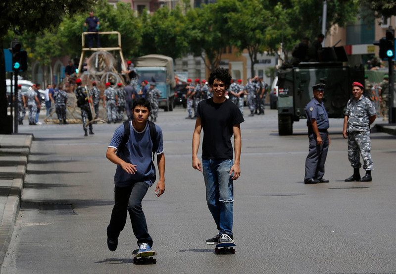 . Two youths on skateboards pass by a police officer and a soldier securing a street they have closed off, where anti-Hezbollah activists had earlier held a protest, in Beirut June 9, 2013. An unarmed Lebanese protester, a member of a small crowd demonstrating against the backing of Iran and its Hezbollah ally for Syrian President Bashar al-Assad, was killed on Sunday by gunfire in front of the Iranian embassy in Beirut, Lebanese security officials said.                REUTERS/ Jamal Saidi