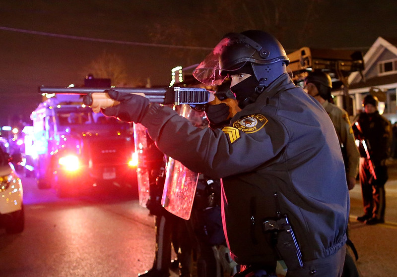 . A police officer points a shotgun at protestors during a demonstration on November 24, 2014 in Ferguson, Missouri. A St. Louis County grand jury has decided to not indict Ferguson police Officer Darren Wilson in the shooting of Michael Brown that sparked riots in Ferguson, Missouri in August.  (Photo by Justin Sullivan/Getty Images)