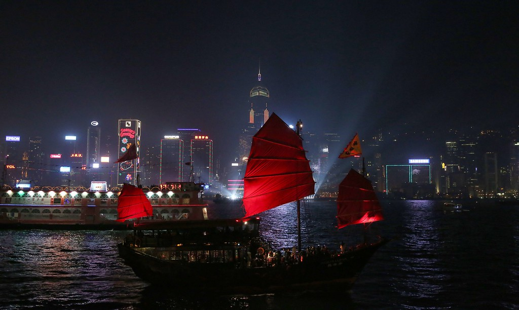 """. An old style \""""Junk Boat\"""" (C) sails Victoria Harbour before the New Year fireworks in Hong Kong on December 31, 2014. Just like previous years, the city\'s iconic skyline along Victoria Harbour will light up with an eight-minute pyrotechnic display, as tens of thousdands of partygoers will flock to the waterfront to celebrate. AFP PHOTO / ISAAC LAWRENCEIsaac Lawrence/AFP/Getty Images"""
