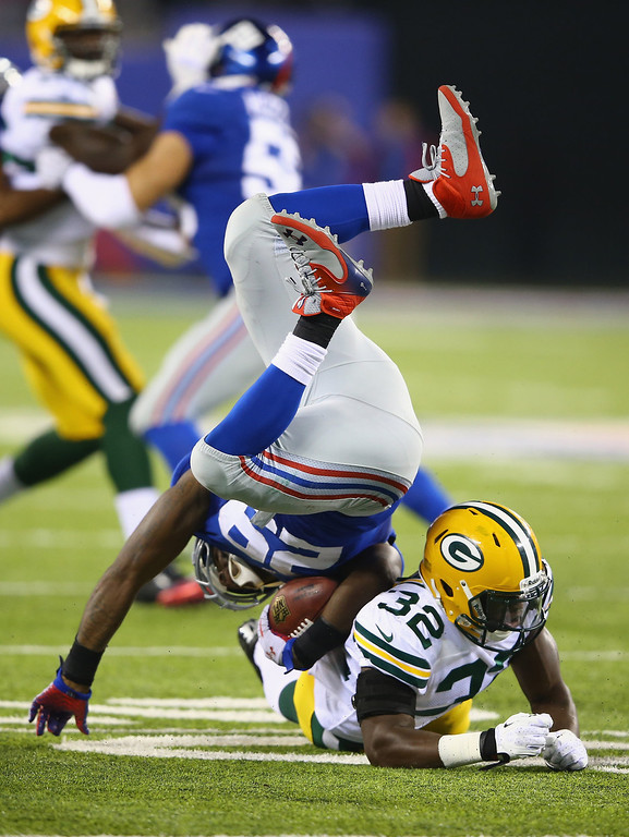 . Chris Banjo #32 of the Green Bay Packers tackles  Michael Cox #29 of the New York Giants  during their game at MetLife Stadium on November 17, 2013 in East Rutherford, New Jersey.  (Photo by Al Bello/Getty Images)