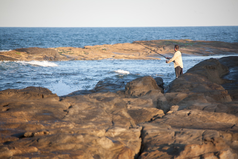 A man fishes with a long fishing pole along the shore in Australia - Woody Head Road 92, Woody Head, New South Wales, Australia (AU)