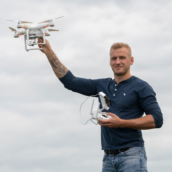 Man holding a drone and remote control, Portrush, The Coastal Route, Northern Ireland, United Kingdom