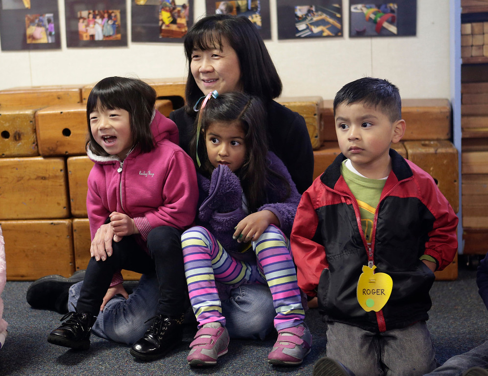 . Akemi Honma,4, Maddie Dhillon,4, and Roger Herrera, 4, and parent volunteer, Lani Honma, participate in a group activity at the Mountain View Parent Nursery School in Mountain View, Calif. on Friday, Feb. 8, 2013. The Mountain View-Whisman School District has decided that if parents hold back an eligible child from kindergarten, it will help evaluate those children for kindergarten-readiness the following year. Some will be sent to first grade rather than kindergarten. (Gary Reyes/ Staff)