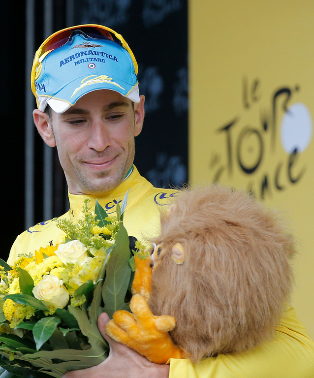 . Italy\'s Vincenzo Nibali, wearing the overall leader\'s yellow jersey,  looks at the trophy as he celebrates on the podium of the fourth stage of the Tour de France cycling race over 163.5 kilometers (101.6 miles) with start in Le Touquet and finish in Lille, France, Tuesday, July 8, 2014. (AP Photo/Christophe Ena)