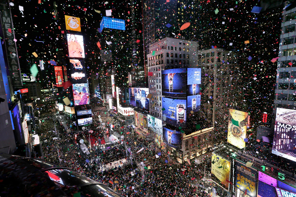 . Confetti drops over the crowd as the clock strikes midnight during the New Year\'s celebration in Times Square as seen from the Marriott Marquis in New York, Monday, Jan. 1, 2018. (AP Photo/Seth Wenig)