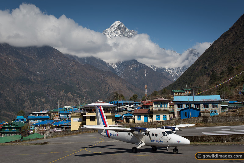 Royal Nepal Airlines Twin Otter aircraft arrives at Lukla airport. Numbur peak behind.