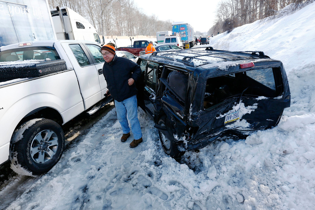 . A man gets out of a SUV, one of many vehicles piled up in an accident, Friday, Feb. 14, 2014, in Bensalem, Pa. Traffic accidents involving multiple tractor trailers and dozens of cars have completely blocked one side of the Pennsylvania Turnpike outside Philadelphia and caused some injuries. (AP Photo/Matt Rourke)