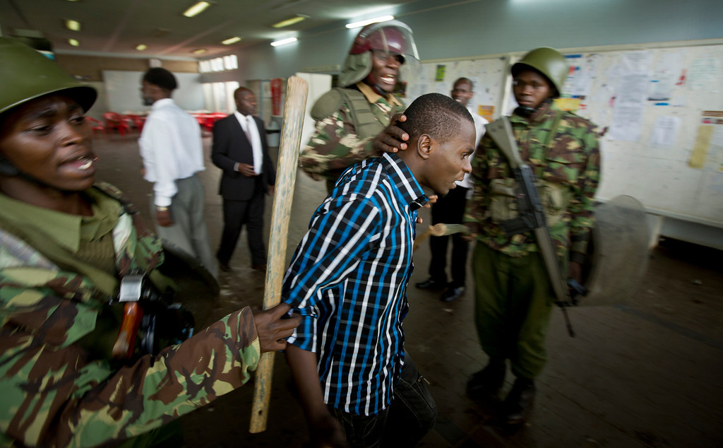 . A Kenyan student is detained by riot police after surrendering in order to escape from a tear-gas-filled building inside Nairobi University\'s main campus in downtown Nairobi, Kenya Tuesday, May 20, 2014. Kenyan university students on Tuesday carried out demonstrations over a proposed increase in student fees, but the protests quickly turned into hours of running battles between students throwing rocks and security forces firing tear gas, before riot police chased the students inside their campus and cornered them in a building into which they fired dozens of tear gas grenades and for a while prevented anyone from leaving. (AP Photo/Ben Curtis)