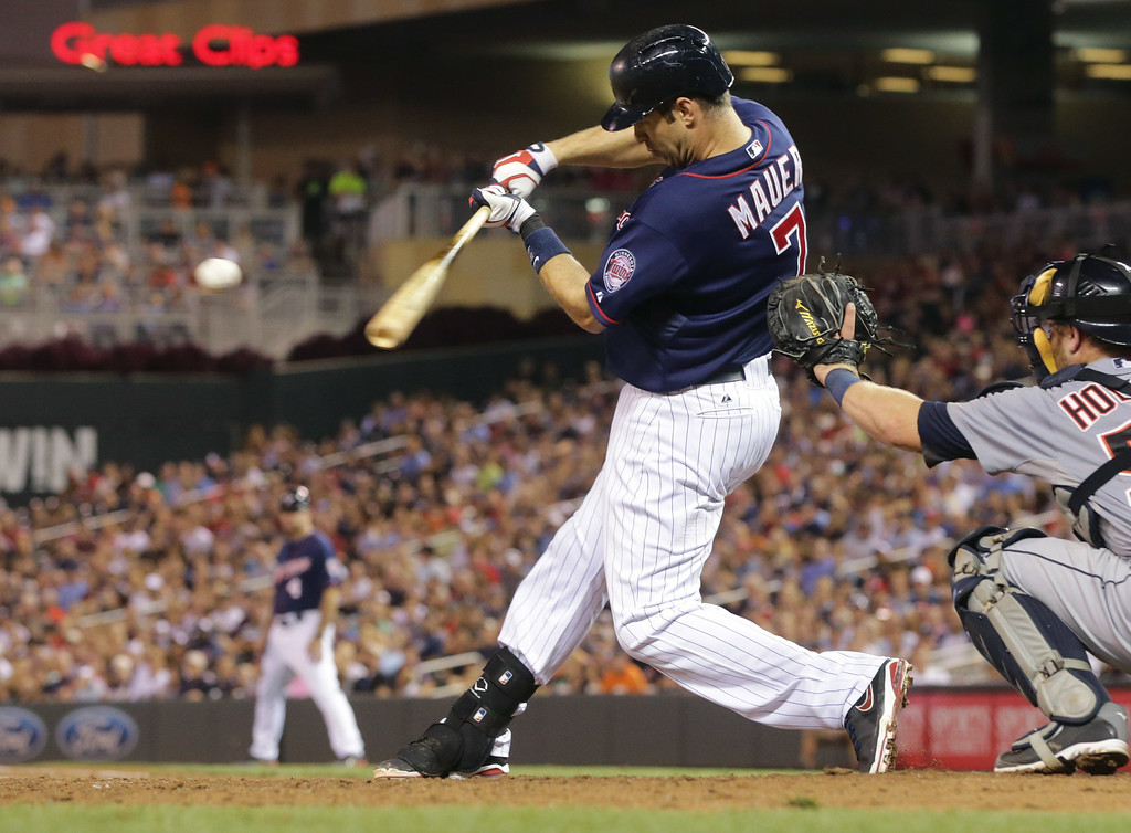 . Minnesota Twins first baseman Joe Mauer  hits a two-run single off Detroit Tigers pitcher Ian Krol in the sixth inning of a baseball game, Friday, Aug. 22, 2014, in Minneapolis. (AP Photo/Jim Mone)