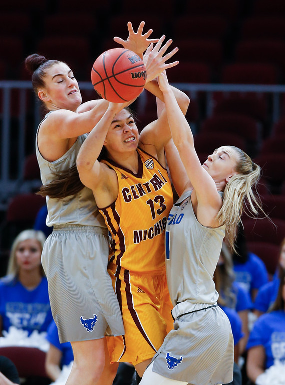. Central Michigan forward Reyna Frost battles Buffalo guard Stephanie Reid, right, and Cassie Oursler, left, for a rebound during the first half of an NCAA college basketball game in the championship of the Mid-American Conference tournament Saturday, March 10, 2018, in Cleveland. Central Michigan won 96-91. (AP Photo/Ron Schwane)
