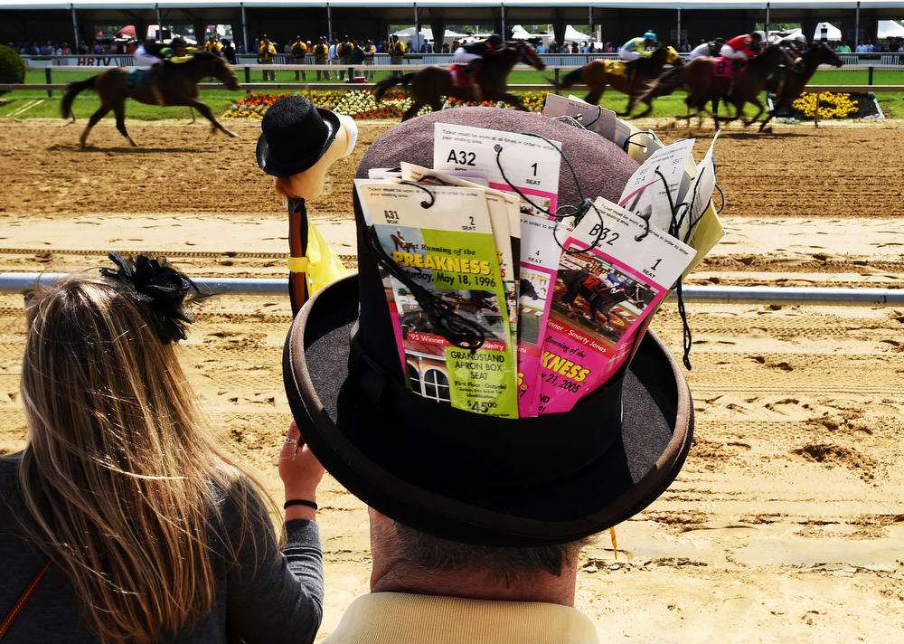 . Fans look on as the field races past during the first race prior to the 139th running of the Preakness Stakes at Pimlico Race Course on May 17, 2014 in Baltimore, Maryland.  (Photo by Molly Riley/Getty Images)