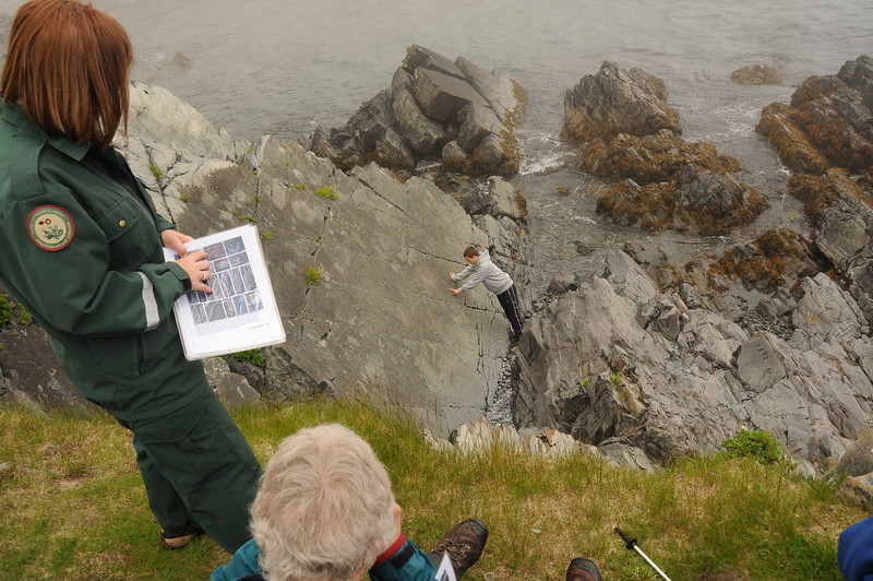 Gretel is pointing out a particular fossil on the page while her assistant is pointing it out on the rock face.