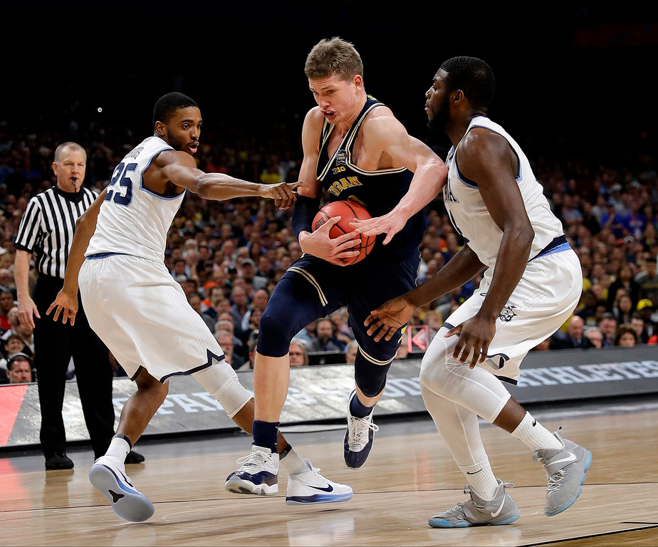 . Michigan\'s Moritz Wagner (13) drives between Villanova\'s Mikal Bridges (25) and Eric Paschall during the first half in the championship game of the Final Four NCAA college basketball tournament, Monday, April 2, 2018, in San Antonio. (AP Photo/David J. Phillip)