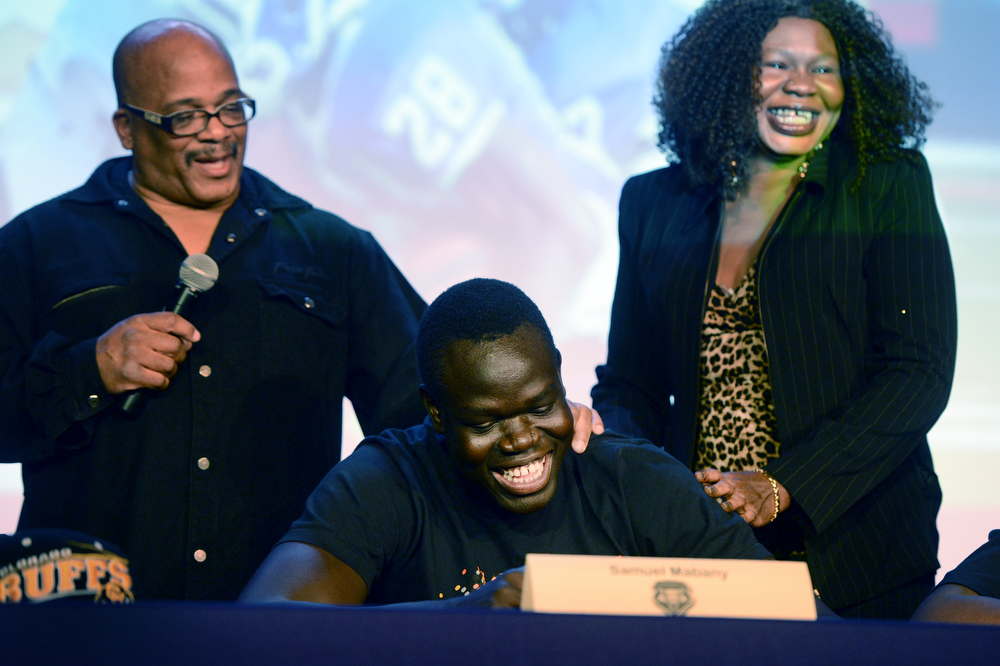 . Denver South High School football coach Tony Lindsay Sr. introduces player Samuel Mabany and his mother, Mary Majok, during a signing day ceremony at the school in Denver, CO February  06, 2013. Mabany signed with the University of New Mexico. (Photo By Craig F. Walker/The Denver Post)