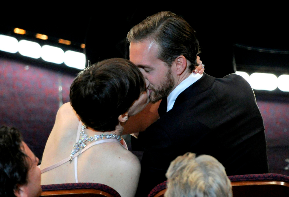Description of . Anne Hathaway, left, kisses Adam Shulman after being announced as the winner of the award for best actress in a supporting role for