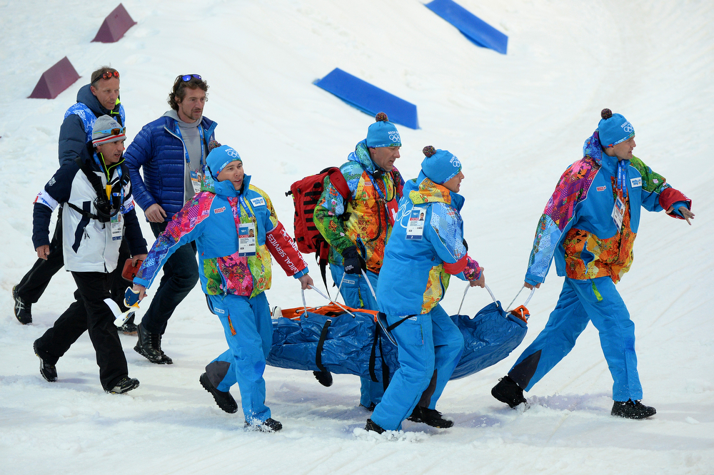 . Marie Laure Brunet of France is carried away by course workers and doctors after collapsing in the snow during the Women\'s 4 x 6 km Relay during day 14 of the Sochi 2014 Winter Olympics at Laura Cross-country Ski & Biathlon Center on February 21, 2014 in Sochi, Russia.  (Photo by Harry How/Getty Images)