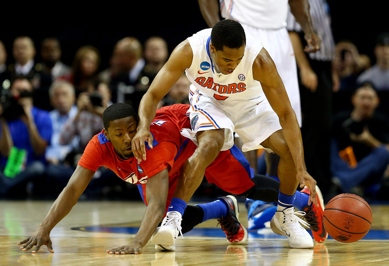 . Scoochie Smith #11 of the Dayton Flyers and Kasey Hill #0 of the Florida Gators battle for a loose ball during the south regional final of the 2014 NCAA Men\'s Basketball Tournament at the FedExForum on March 29, 2014 in Memphis, Tennessee.  (Photo by Streeter Lecka/Getty Images)