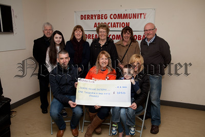 Cathryn Gibson from Muscular Dystrophy Campaign accepts a cheque for £1050 from Martin Moore, Hazel O'Hare and Family money raised through a table quiz held in Derrybeg Community Centre on the 6th February. R1510001