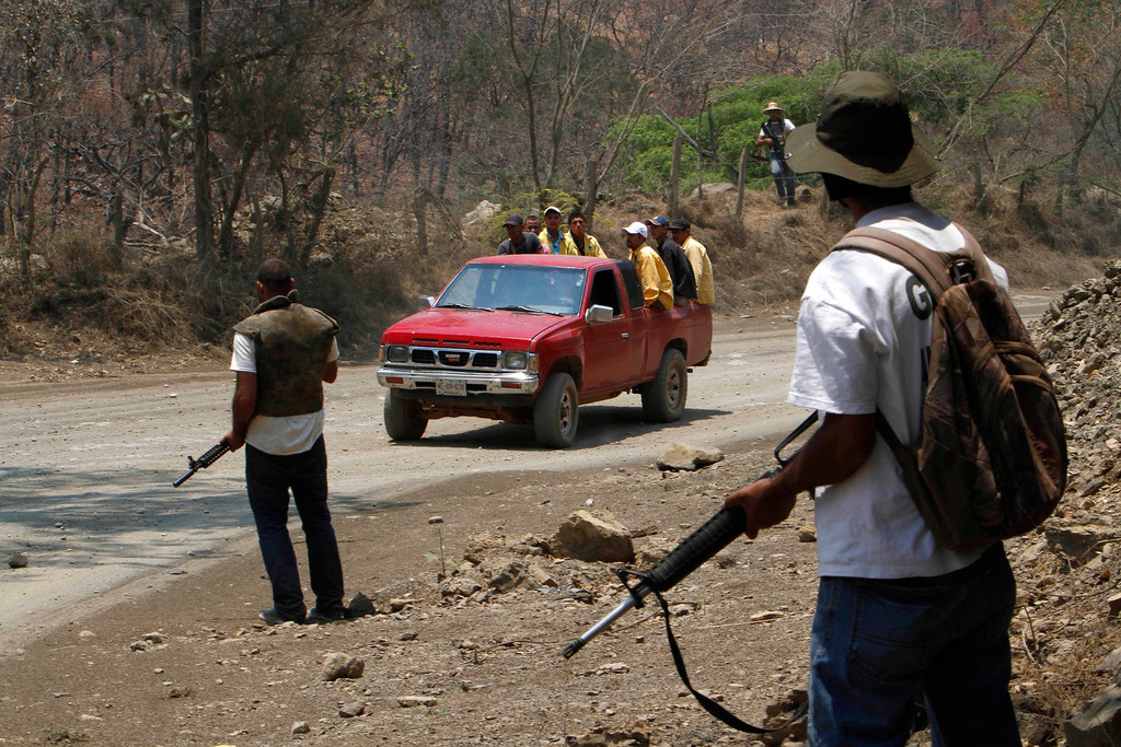 . In this May 20, 2013 photo, armed men belonging to a local self-defense group stand guard as a vehicle approaches at the entrance of the town of Cualcoman, Mexico.  Self-defense groups started to spring up in February to fight back the Knights Templar drug cartel which is extorting protection payments from cattlemen and lime growers, butchers and even marijuana growers. The federal government sees both the self-defense forces and the cartel as dangerous enemies. (AP Photo/Marco Ugarte)