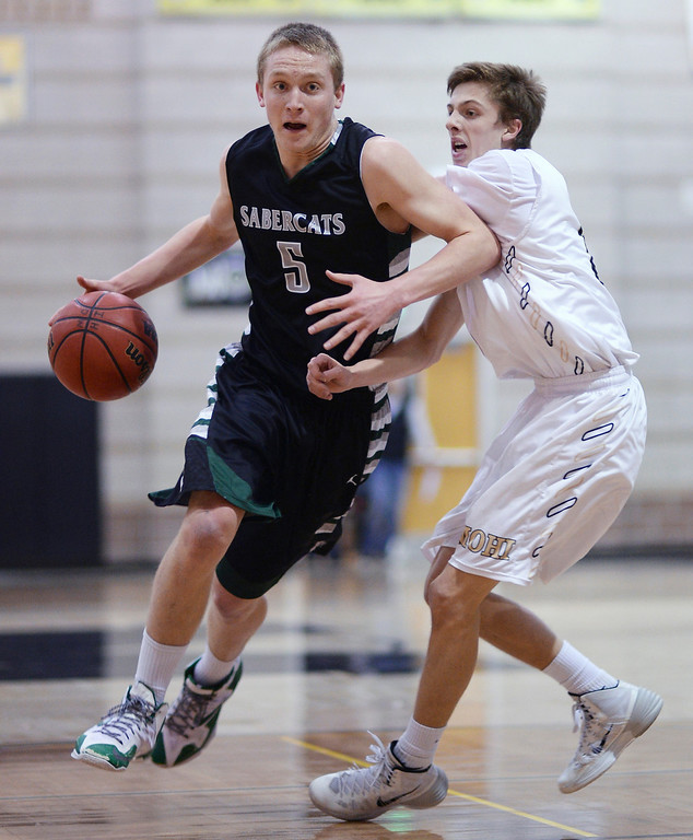 . Brandon Bodnar of Fossil Ridge High School (5), left, controls the ball against Sam Fredricksmeyer of Monarch High School (5) in the 1st half of the game at Monarch High School Gym.   (Photo by Hyoung Chang/The Denver Post)
