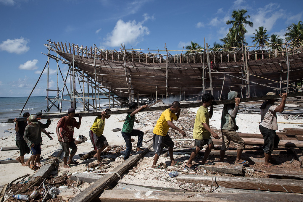 . Buginese men carry a wooden block at Tanjung Bira Beach on May 2, 2014 in Bulukumba, South Sulawesi, Indonesia.  (Photo by Agung Parameswara/Getty Images)