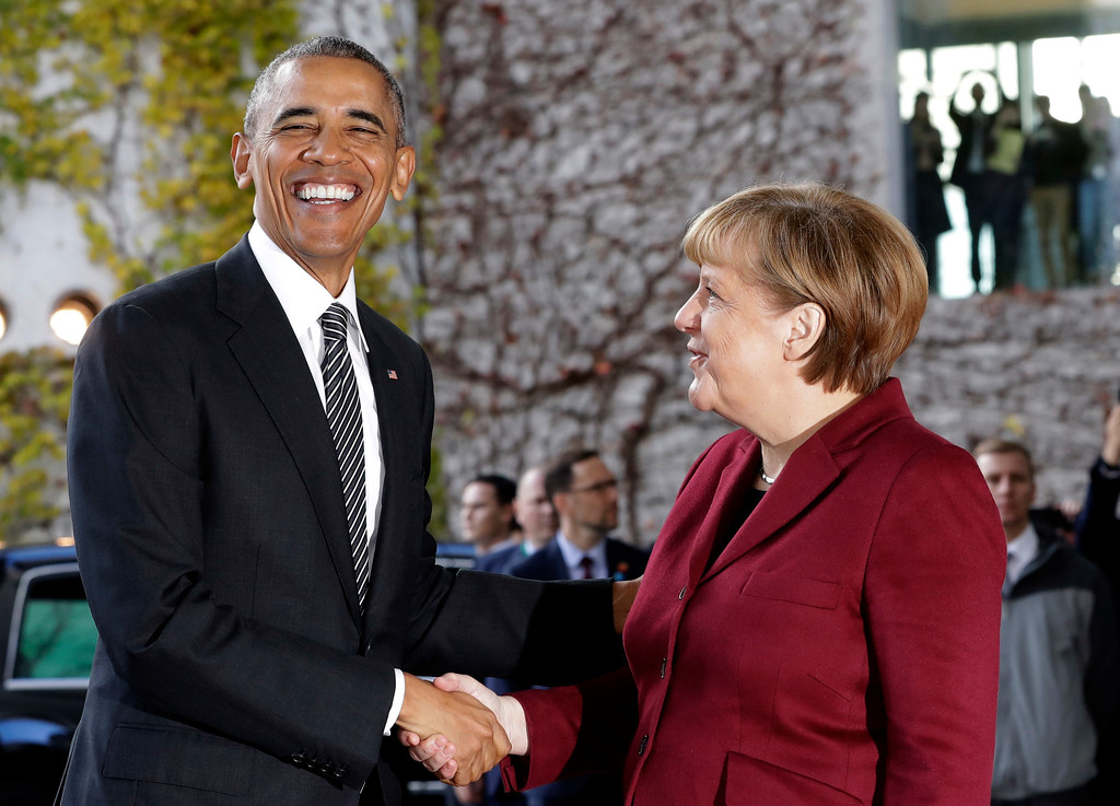 . U.S. President Barack Obama, left, is welcomed by German Chancellor Angela Merkel prior to a meeting of the government heads of Germany, France, Italy, Spain and Britain with U.S. President Obama in the chancellery in Berlin, Germany, Friday, Nov. 18, 2016. (AP Photo/Michael Sohn)