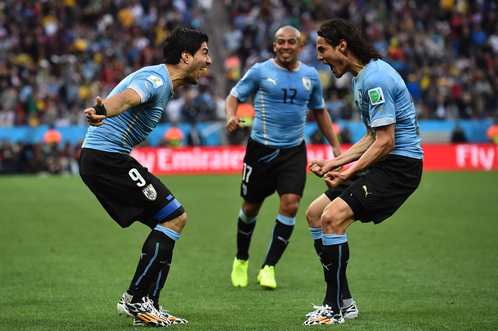 . Uruguay\'s forward Luis Suarez (L) celebrates scoring with teammates Uruguay\'s forward Edinson Cavani (R) and Uruguay\'s midfielder Egidio Arevalo Rios (C) during the Group D football match between Uruguay and England at the Corinthians Arena in Sao Paulo on June 19, 2014, during the 2014 FIFA World Cup. (BEN STANSALL/AFP/Getty Images)