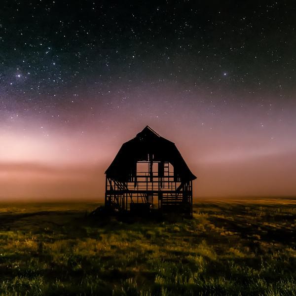 A stripped barn during a foggy night