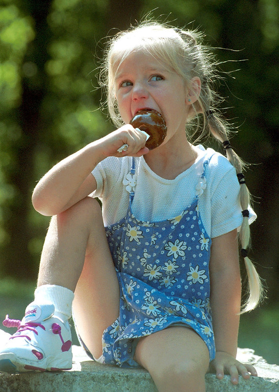 . Millina Kacmar, 4, of Eastpointe, enjoys a caramel apple at Yates Cider Mill in Rochester Hills Friday.