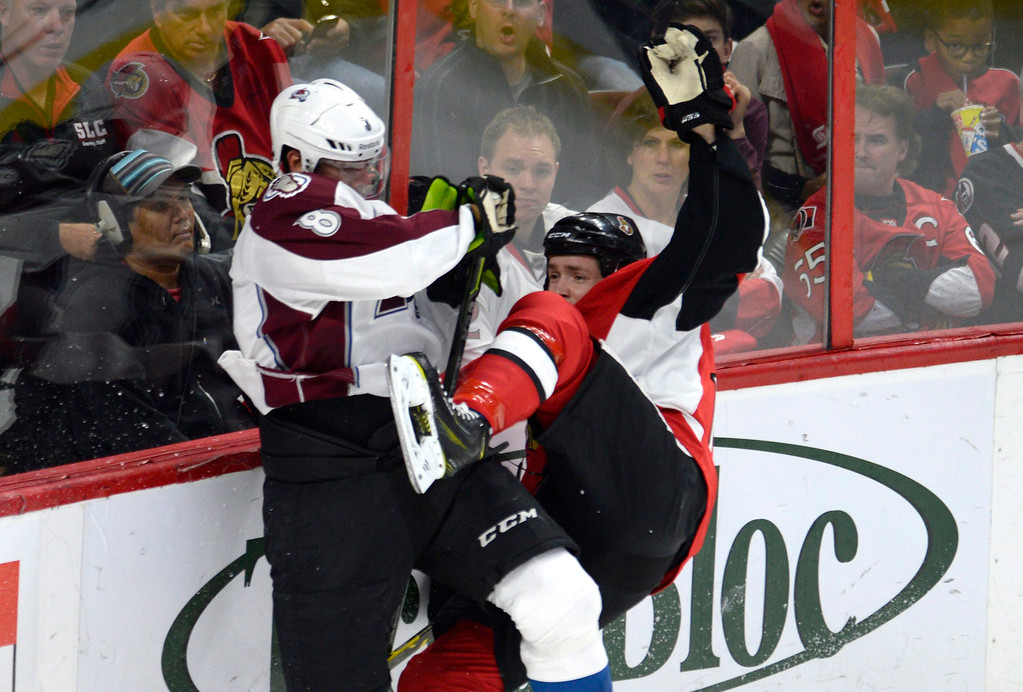 . Colorado Avalanche\'s Jan Hejda (8) collides with Ottawa Senators\' Zack Smith (15) during the first period of an NHL hockey game Thursday, Oct. 16, 2014, in Ottawa, Ontario. (AP Photo/The Canadian Press, Justin Tang)