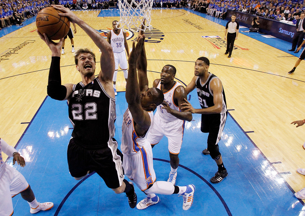 . San Antonio Spurs center Tiago Splitter (22) shoots in front of Oklahoma City Thunder forward Serge Ibaka (9) in the first quarter of Game 3 of an NBA basketball playoff series in the Western Conference finals, Sunday, May 25, 2014, in Oklahoma City. (AP Photo/Sue Ogrocki)
