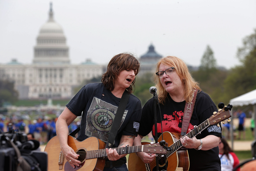 ". Amy Ray (L) and Emily Saliers of The Indigo Girls perform during a demonstration against the proposed Keystone XL pipeline on the National Mall April 22, 2014 in Washington, DC. As part of its ""Reject and Protect\"" protest, the Cowboy and Indian Alliance is organizing a weeklong series of actions by farmers, ranchers and tribes to show their opposition to the pipeline.  (Photo by Chip Somodevilla/Getty Images)"