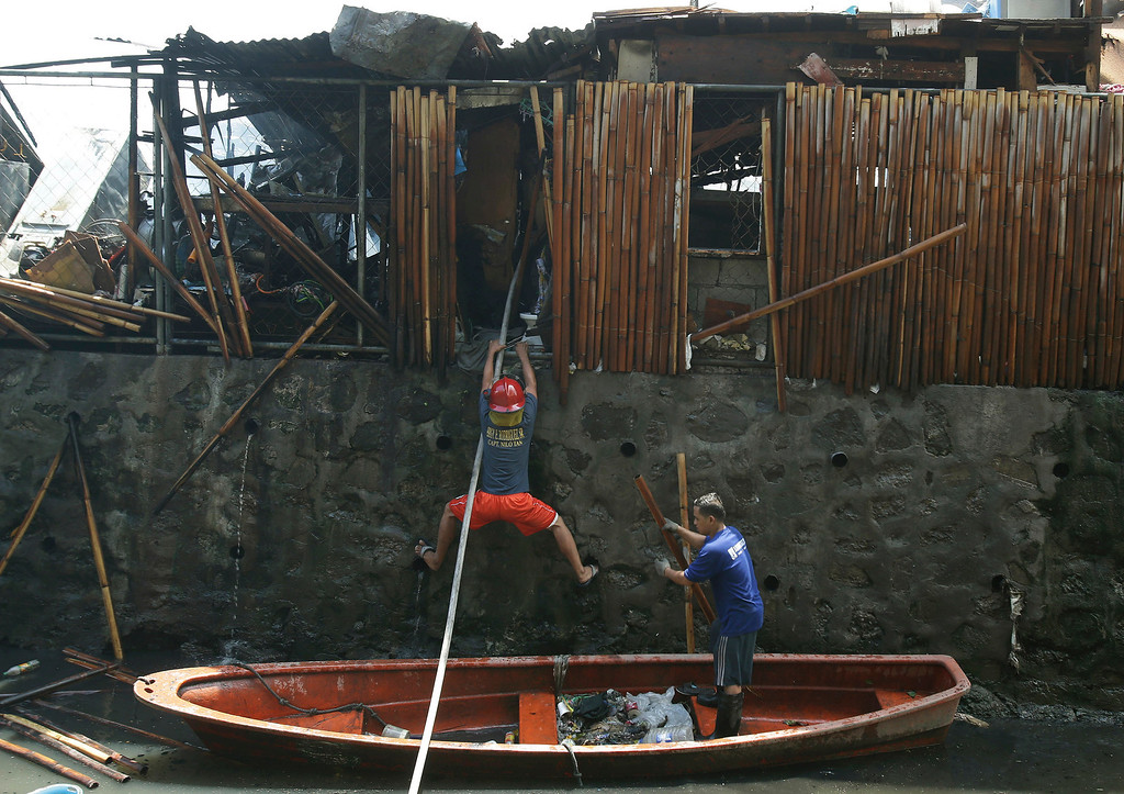 . A Filipino fire volunteer climbs up a wall while assisting in controlling a fire that gutted a residential area at the financial district of Makati, south of Manila, Philippines on Thursday, July 11, 2013. Investigators are still checking the cause of the fire which gutted a slum colony and left hundreds homeless. (AP Photo/Aaron Favila)
