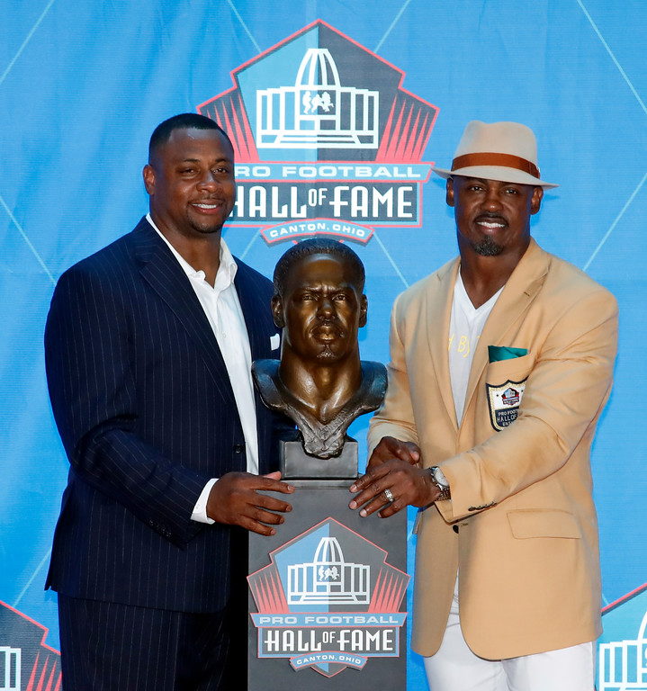 . Former NFL safety Brian Dawkins, right, poses with a bust of himself and with his presenter, former teammate Troy Vincent, during inductions at the Pro Football Hall of Fame, Saturday, Aug. 4, 2018 in Canton, Ohio. (AP Photo/Gene J. Puskar)