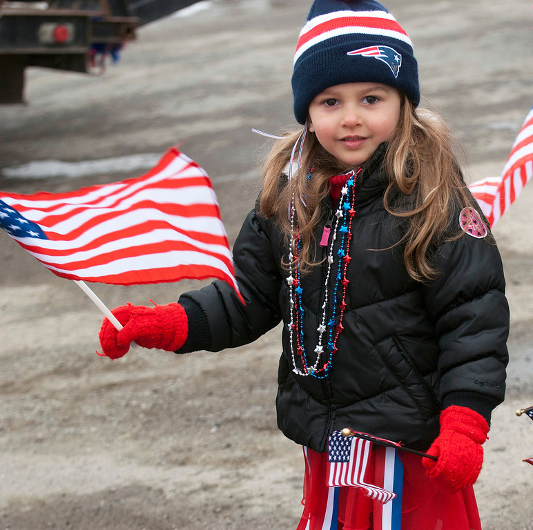 """. Kayla Rice/Reformer                                 A patriotically dressed girl holds American flags for the \""""Devin Day\"""" parade and celebration in Dover on Saturday."""