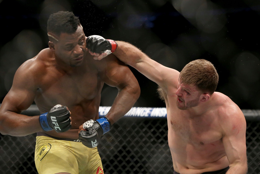 . Stipe Miocic lands a right hand against Francis Ngannou during a heavyweight championship mixed martial arts bout at UFC 220, early Sunday, Jan. 21, 2018, in Boston. Miocic retained his title via unanimous decision. (AP Photo/Gregory Payan)