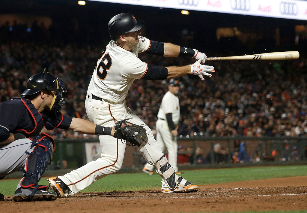 . San Francisco Giants\' Buster Posey hits an RBI single in front of Cleveland Indians catcher Yan Gomes during the sixth inning of a baseball game in San Francisco, Tuesday, July 18, 2017. (AP Photo/Jeff Chiu)