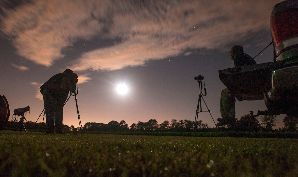 . Photographers Chuck Vickers, right, and James Taylor photograph the lunar eclipse Wednesday, Oct. 8, 2014 morning from a large field south of Wade, N.C. The moon appears orange or red, the result of sunlight scattering off Earth\'s atmosphere. This is known as the blood moon. (AP Photo/The Fayetteville Observer, Johnny Horne)