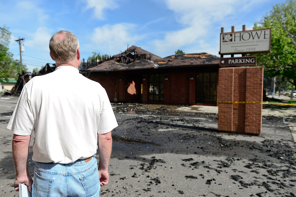 . Owner Geoff Howe surveys the damage to the building, Tuesday, May 28, 2013, at Howe Mortuary and Cremation Services in Longmont.  An overnight fire at the mortuary caused the roof to collapse.  (AP Photo/The Daily Times Call,  Matthew Jonas )