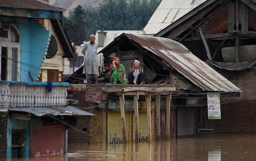 . Flood-affected Kashmiris shout out for help from the roof of a house in Srinagar, India, Tuesday, Sept. 9, 2014.   (AP Photo/Altaf Qadri)