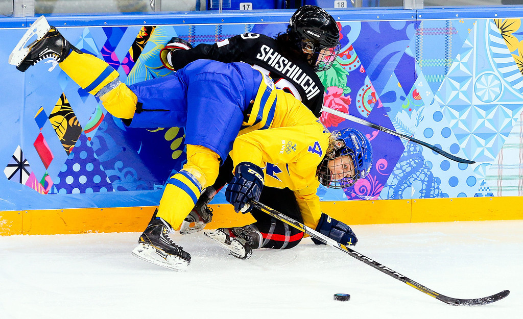 . Jenni Asserholt (front) of Sweden fights for the puck with Miho Shishiuchi (back) of Japan during the match between Sweden and Japan at the Shayba Arena in the Ice Hockey tournament at the Sochi 2014 Olympic Games, Sochi, Russia, 09 February 2014.  EPA/SRDJAN SUKI